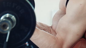 Κινηματογράφηση σε πρώτο πλάνο του ατόμου που κάνει τις μπούκλες δικέφαλων μυών απόθεμα βίντεο