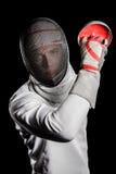 Κινηματογράφηση σε πρώτο πλάνο του ατόμου που φορά την άσκηση κοστουμιών περίφραξης με το ξίφος Στοκ Φωτογραφία