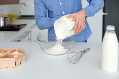Κινηματογράφηση σε πρώτο πλάνο του ατόμου στο μπλε πουκάμισο που προετοιμάζει τη ζύμη στην κουζίνα Στοκ φωτογραφία με δικαίωμα ελεύθερης χρήσης