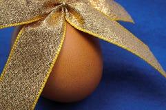 Κινηματογράφηση σε πρώτο πλάνο του αυγού Πάσχας που δένεται από τη χρυσή κορδέλλα Στοκ Εικόνα