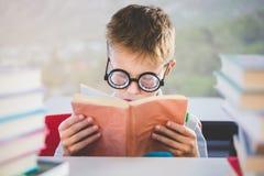 Κινηματογράφηση σε πρώτο πλάνο του βιβλίου ανάγνωσης schoolkid στην τάξη Στοκ φωτογραφία με δικαίωμα ελεύθερης χρήσης