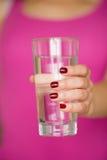 Κινηματογράφηση σε πρώτο πλάνο του γυαλιού χεριών της γυναίκας holdong του γλυκού νερού Στοκ Εικόνα