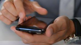 Κινηματογράφηση σε πρώτο πλάνο του επιχειρηματία που χρησιμοποιεί το τηλέφωνο κυττάρων απόθεμα βίντεο