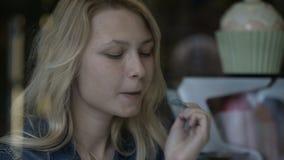 Κινηματογράφηση σε πρώτο πλάνο του ευτυχούς ξανθού κοριτσιού εφήβων που τρώει το παγωτό στο εστιατόριο που απολαμβάνει το γλυκό ε απόθεμα βίντεο