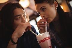 Κινηματογράφηση σε πρώτο πλάνο του ζεύγους που έχει milkshake Στοκ Εικόνες