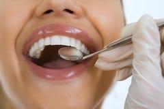 Κινηματογράφηση σε πρώτο πλάνο του θηλυκού ασθενή που έχει τα δόντια της εξετασμένων από τον οδοντίατρο Στοκ Εικόνα