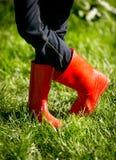 Κινηματογράφηση σε πρώτο πλάνο του κοριτσιού στις κόκκινες λαστιχένιες μπότες που θέτουν στη φρέσκια πράσινη χλόη Στοκ Φωτογραφία