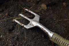 Κινηματογράφηση σε πρώτο πλάνο του μικρού δικράνου κηπουρικής στο χώμα στοκ εικόνες