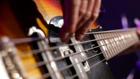 Κινηματογράφηση σε πρώτο πλάνο του μουσικού που παίζει τη βαθιά κιθάρα στη συναυλία στο νυχτερινό κέντρο διασκέδασης με το φως απόθεμα βίντεο