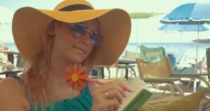 Κινηματογράφηση σε πρώτο πλάνο του νέου ξανθού γραψίματος γυναικών στο σημειωματάριο απόθεμα βίντεο