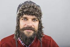 Κινηματογράφηση σε πρώτο πλάνο του νεαρού άνδρα με τη γενειάδα που φορά ένα χειμερινό καπέλο Στοκ Εικόνα
