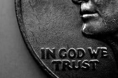 Κινηματογράφηση σε πρώτο πλάνο του νομίσματος με στο Θεό εμπιστευόμαστε Στοκ Φωτογραφία