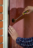 Κινηματογράφηση σε πρώτο πλάνο του ξυλουργού που προσπαθεί στην κλειδαριά ανοιχτών πορτών που χρησιμοποιεί το κατσαβίδι στοκ εικόνες