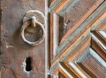 Κινηματογράφηση σε πρώτο πλάνο του οξυδωμένου εξογκώματος πορτών δαχτυλιδιών πέρα από μια ηλικίας διακοσμημένη ξύλινη πόρτα Στοκ φωτογραφίες με δικαίωμα ελεύθερης χρήσης