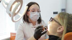 Κινηματογράφηση σε πρώτο πλάνο του οδοντιάτρου που εξετάζει τα νέα δόντια γυναικών ` s απόθεμα βίντεο