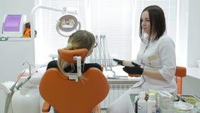 Κινηματογράφηση σε πρώτο πλάνο του οδοντιάτρου που εξετάζει τα νέα δόντια γυναικών ` s φιλμ μικρού μήκους