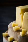 Κινηματογράφηση σε πρώτο πλάνο του σουηδικού σκληρού κίτρινου τυριού με τις τρύπες που τεμαχίζονται στις ξύλινες φέτες Στοκ εικόνες με δικαίωμα ελεύθερης χρήσης
