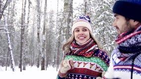 Κινηματογράφηση σε πρώτο πλάνο του συμπαθητικού νέου ζεύγους που τρέχει στο δάσος σε ένα χειμερινό πρωί φιλμ μικρού μήκους