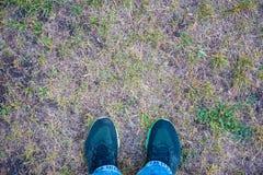 Κινηματογράφηση σε πρώτο πλάνο του τρεξίματος των παπουτσιών στη χλόη - εικόνα έννοιας στοκ εικόνα