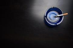 Κινηματογράφηση σε πρώτο πλάνο του τσιγάρου ashtray Στοκ Εικόνα