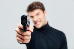 Κινηματογράφηση σε πρώτο πλάνο του υ νεαρού άνδρα που δείχνει με το πυροβόλο όπλο σε σας Στοκ φωτογραφία με δικαίωμα ελεύθερης χρήσης