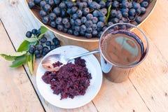 Κινηματογράφηση σε πρώτο πλάνο του φρέσκου χυμού και μαρμελάδα του ώριμου μαύρου chokeberry melanocarpa Aronia Στοκ Εικόνα