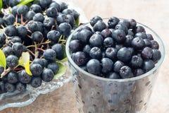 Κινηματογράφηση σε πρώτο πλάνο του φρέσκου ώριμου μαύρου chokeberry melanocarpa Aronia με τα φύλλα στο δοχείο γυαλιού στο καφετί  Στοκ Φωτογραφία