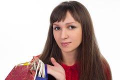 Κινηματογράφηση σε πρώτο πλάνο του χαμογελώντας κοριτσιού στις αγορές με τις ζωηρόχρωμες τσάντες εγγράφου Στοκ Εικόνες