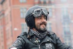 Κινηματογράφηση σε πρώτο πλάνο του χαμογελώντας ποδηλάτη που φορά τα ενδύματα δέρματος Στοκ Φωτογραφία