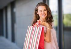 Κινηματογράφηση σε πρώτο πλάνο του χαμόγελου, καφετής-μαλλιαρή γυναίκα που κρατά μια τσάντα stripey Στοκ Εικόνα