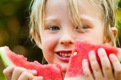 Κινηματογράφηση σε πρώτο πλάνο του χαριτωμένου ευτυχούς παιδιού που τρώει το καρπούζι Στοκ Φωτογραφίες