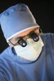 Κινηματογράφηση σε πρώτο πλάνο του χειρούργου που φορά τη μάσκα και την ενίσχυση - γυαλιά Στοκ Εικόνα