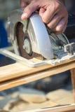 Κινηματογράφηση σε πρώτο πλάνο του χειρώνακτα που χρησιμοποιεί το κυκλικό πριόνι Στοκ Φωτογραφίες