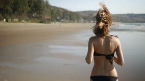 Κινηματογράφηση σε πρώτο πλάνο του όμορφου νέου κοριτσιού που τρέχει κατά μήκος της παραλίας υγιής τρόπος ζωής έννοιας κίνηση αργ απόθεμα βίντεο