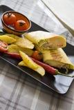 Κινηματογράφηση σε πρώτο πλάνο του burrito με την τηγανισμένη πατάτα στο μαύρο πιάτο Στοκ Εικόνες