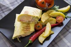 Κινηματογράφηση σε πρώτο πλάνο του burrito με την τηγανισμένη πατάτα στο μαύρο πιάτο Στοκ εικόνα με δικαίωμα ελεύθερης χρήσης