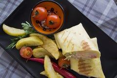 Κινηματογράφηση σε πρώτο πλάνο του burrito με την τηγανισμένη πατάτα στο μαύρο πιάτο Στοκ Φωτογραφίες