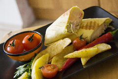 Κινηματογράφηση σε πρώτο πλάνο του burrito στο μαύρο πιάτο Στοκ Εικόνες