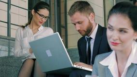 Κινηματογράφηση σε πρώτο πλάνο των έξυπνων επιχειρηματιών που κάθονται στα σκαλοπάτια με το κτίριο γραφείων και που χρησιμοποιούν απόθεμα βίντεο