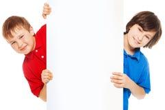 Κινηματογράφηση σε πρώτο πλάνο των αγοριών που παρουσιάζουν νέα κενή διαφήμιση Στοκ Φωτογραφίες