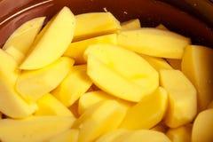 Κινηματογράφηση σε πρώτο πλάνο των ακατέργαστων ξεφλουδισμένων πατατών στο δοχείο ή το τηγάνι. Υγιή τρόφιμα. Στοκ Εικόνες