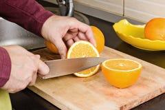 Κινηματογράφηση σε πρώτο πλάνο των ανθρώπινων χεριών που κόβουν τα πορτοκάλια Στοκ Φωτογραφία