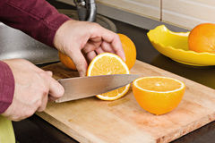 Κινηματογράφηση σε πρώτο πλάνο των ανθρώπινων χεριών που κόβουν τα πορτοκάλια Στοκ φωτογραφία με δικαίωμα ελεύθερης χρήσης