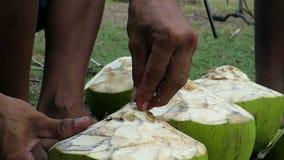 Κινηματογράφηση σε πρώτο πλάνο των ανθρώπινων χεριών που προετοιμάζουν τη φρέσκια πράσινη καρύδα απόθεμα βίντεο