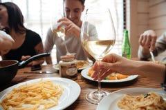 Κινηματογράφηση σε πρώτο πλάνο των ανθρώπων που πίνουν το κρασί και που τρώνε τα ζυμαρικά στον πίνακα Στοκ Φωτογραφίες
