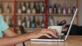Κινηματογράφηση σε πρώτο πλάνο των αρσενικών χεριών που χρησιμοποιούν το lap-top στον καφέ φιλμ μικρού μήκους