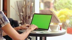 Κινηματογράφηση σε πρώτο πλάνο των αρσενικών χεριών που χρησιμοποιούν το lap-top στον καφέ με την πράσινη οθόνη φιλμ μικρού μήκους