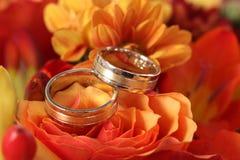 Κινηματογράφηση σε πρώτο πλάνο των γαμήλιων δαχτυλιδιών στο υπόβαθρο των λουλουδιών Στοκ Φωτογραφίες
