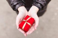 Κινηματογράφηση σε πρώτο πλάνο των θηλυκών χεριών με τα σακάκια που κρατούν ένα κόκκινο παρόν με Στοκ Εικόνα