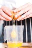 Κινηματογράφηση σε πρώτο πλάνο των θηλυκών χεριών που σπάζουν ένα αυγό Στοκ Εικόνες